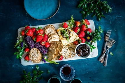 Picture of plate with cheese, crackers, and strawberries.and