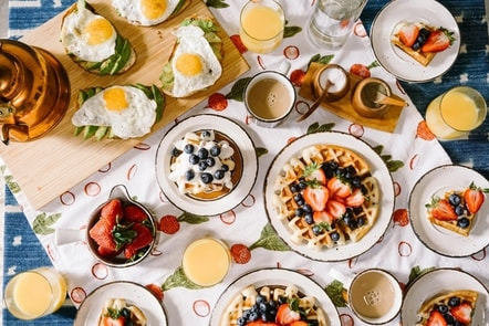 Picture of plates with different breakfast foods, including waffles with whipped cream and berries, eggs, and orange juice.