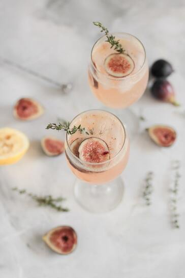 Pink cocktail in wine glass with herb and fruit garnish