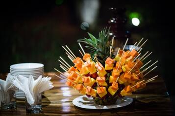 Fruit kebabs poking into a pineapple