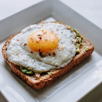 Picture of avocado toast with fried egg on top, on a fancy square plate.